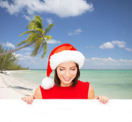 christmas, x-mas, people, advertisement and sale concept - happy woman in santa helper hat with blank white board over tropical beach background photo