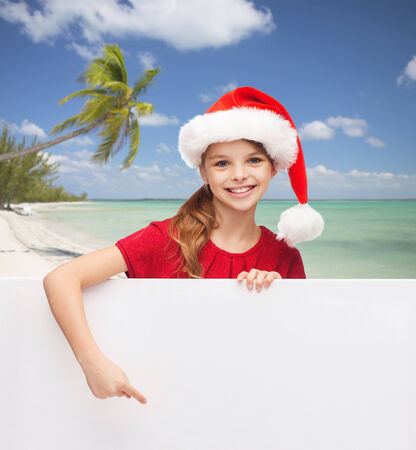 christmas, holidays, people, advertisement and sale concept - happy little girl in santa helper hat with blank white board over tropical beach background photo