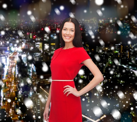 christmas, holidays, celebration and people concept - smiling woman in red dress over snowy night city background photo