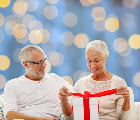 family, holidays, christmas, age and people concept - happy senior couple with gift box over blue lights background photo