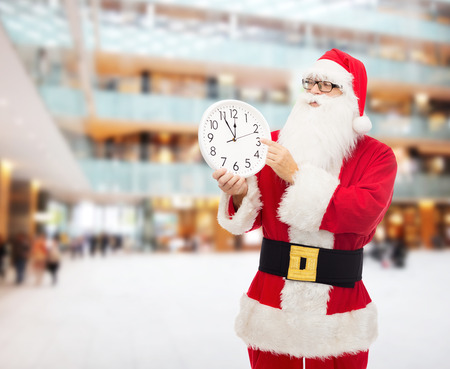 12 oclock: christmas, holidays and people concept - man in costume of santa claus with clock showing twelve pointing finger over shopping center background