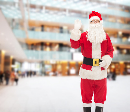 christmas, holidays, gesture and people concept - man in costume of santa claus waving hand over shopping center background photo