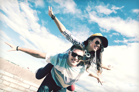 flying man: summer holidays and teenage concept - teenagers having fun outside