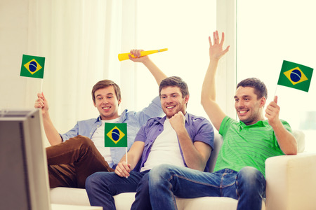 vuvuzela: friendship, sports and entertainment concept - happy male friends with flags and vuvuzela supporting football team at home