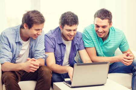 friendship, technology and home concept - smiling male friends with laptop computer at home Stock Photo