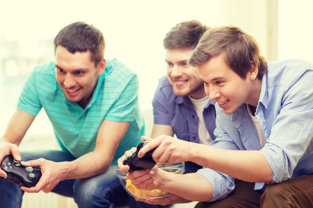 the game: friendship, technology, games and home concept - smiling male friends playing video games at home