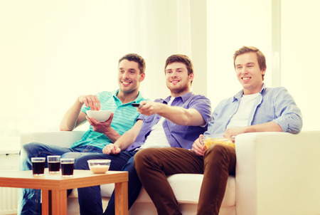 junk: friendship, technology and home concept - smiling male friends with remote control and junk food at home