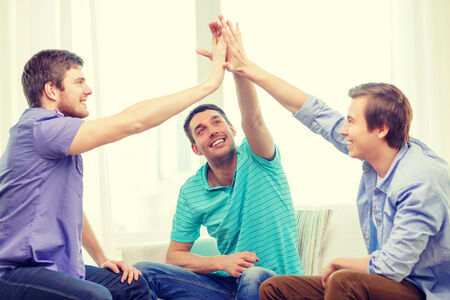 teamwork, friendship and happiness concept - smiling male friends giving high five at home Stock Photo