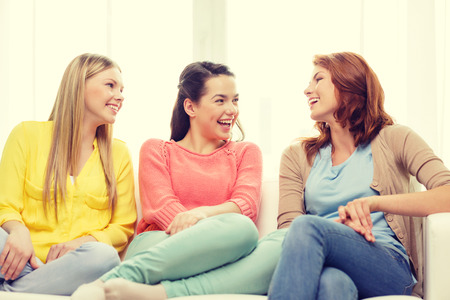 hanging woman: friendship and happiness concept - three girlfriends having a talk at home