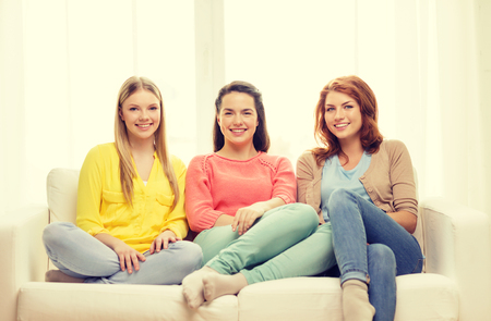 speak out: friendship and happiness concept - three girlfriends having a talk at home