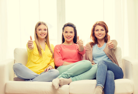 friendship, gesture and happiness concept - three girlfriends showing thumbs up at home photo