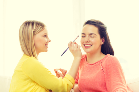 chilling out: makeup, friendship and leisure concept - two smiling teenage girls applying make up at home