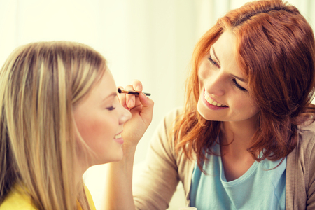 makeup, friendship and leisure concept - two smiling teenage girls applying make up at home