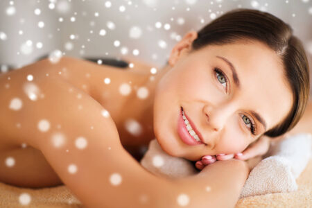 beauty, health, people and spa concept - beautiful woman in spa salon getting hot stones massage photo