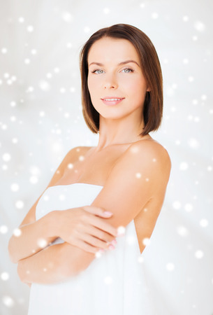 beauty, spa and people concept - beautiful woman standing in\ towel over snowy background