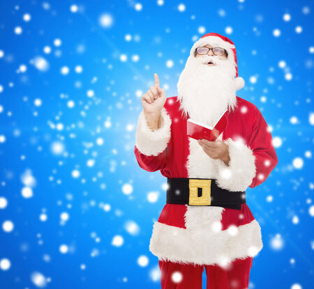 nicolas: christmas, holidays, gesture and people concept - man in costume of santa claus with notepad pointing finger up over blue snowy background