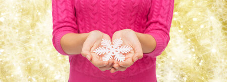 christmas, holidays and people concept - close up of woman in pink sweater holding snowflake over yellow background photo