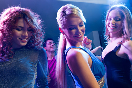 nightclub: party, holidays, celebration, nightlife and people concept - smiling friends dancing in club