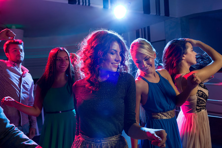 girls night out: party, holidays, celebration, nightlife and people concept - smiling friends dancing in club