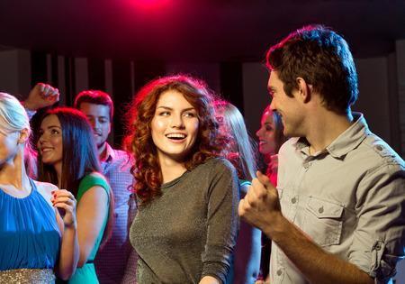 persone che ballano: partito, feste, celebrazioni, vita notturna e persone Concetto - sorridente amici ballare in circolo