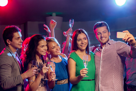 people having fun: party, holidays, technology, nightlife and people concept - smiling friends with glasses of champagne and smartphone taking selfie in club