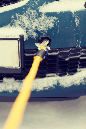 transportation, winter and vehicle concept - closeup of towed car with towing rope photo