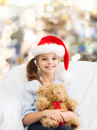 holidays, presents, christmas, childhood and people concept - smiling little girl with teddy bear toy over lights background photo