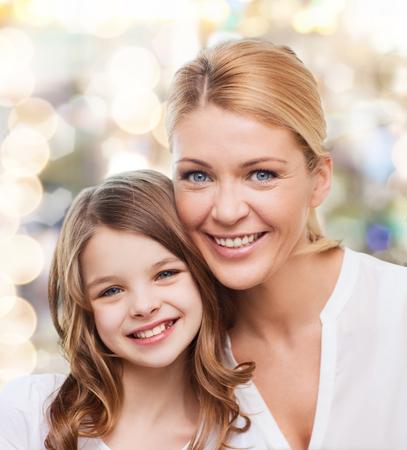 madre e hija adolescente: la familia, la infancia, la felicidad y la gente - madre sonriente y ni�a sobre fondo de las luces