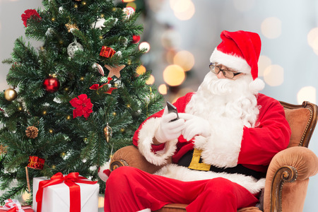 old cell phone: holidays, technology and people concept - man in costume of santa claus with smartphone, presents and christmas tree sitting in armchair over lights background