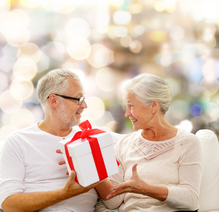 family, holidays, christmas, age and people concept - happy senior couple with gift box over lights background photo