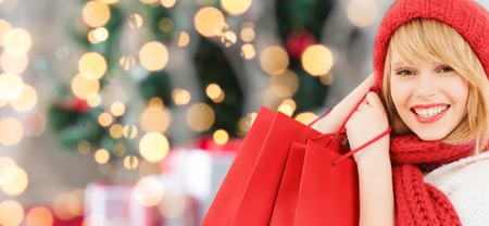 woman shopping: happiness, winter holidays and people concept - smiling young woman in hat and scarf with red shopping bags over christmas tree background