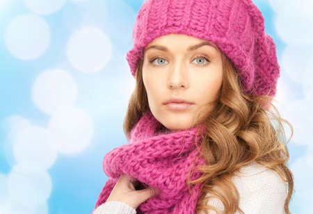 sweater girl: happiness, winter holidays, christmas and people concept - close up of young woman in pink hat and scarf over blue lights background