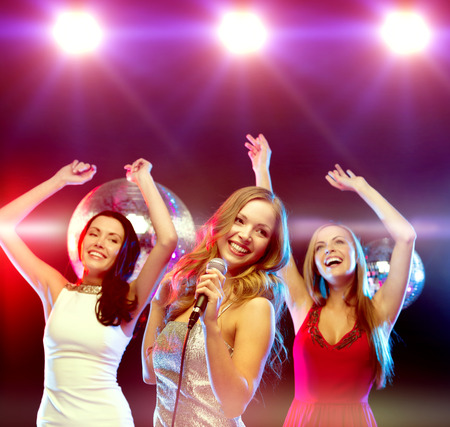 karaoke: new year, celebration, friends, bachelorette party, birthday concept - three women in evening dresses dancing and singing karaoke