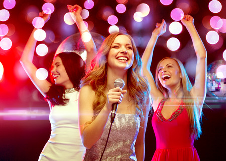 disco lights: new year, celebration, friends, bachelorette party, birthday concept - three women in evening dresses dancing and singing karaoke