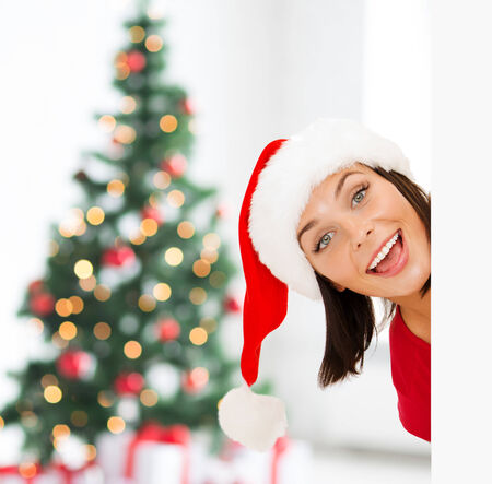 x-mas, people, advertisement and sale concept - happy woman in santa helper hat with blank white board over living room and christmas tree background photo
