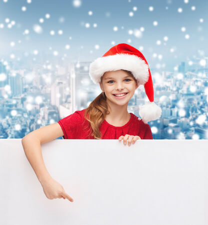 christmas, holidays, people, advertisement and sale concept - happy little girl in santa helper hat with blank white board over snowy city background photo