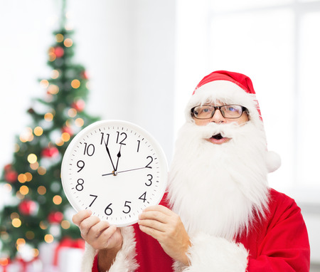 twelve month old: christmas, holidays and people concept - man in costume of santa claus with clock showing twelve pointing finger over living room with tree background