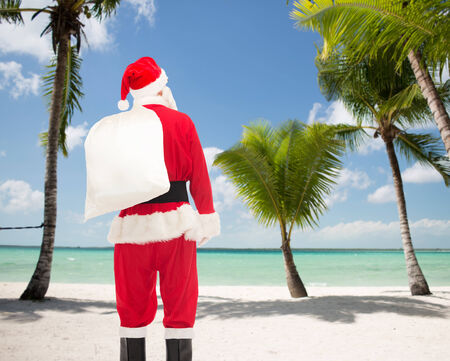 christmas, holidays and people concept - man in costume of santa claus with bag from back over tropical beach background photo