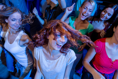 nightclub crowd: party, holidays, celebration, nightlife and people concept - smiling friends dancing in club