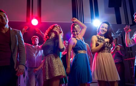 despedida de soltera: fiesta, días de fiesta, celebración, vida nocturna y Concepto - sonriente amigos bailando en el club Foto de archivo