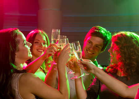 champagne toast: party, holidays, celebration, nightlife and people concept - smiling friends with glasses of champagne in club