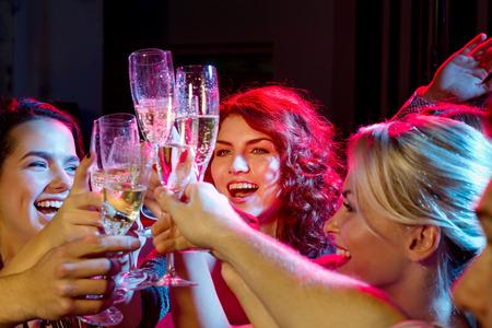 New Year: zabawy, święta, uroczystości, nocne życie i koncepcji ludzi - uśmiecha przyjaciele z kieliszki szampana w klubie
