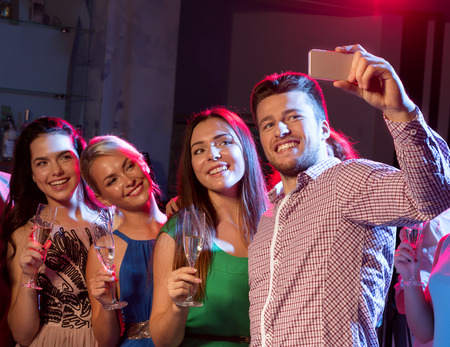 dancing club: party, holidays, technology, nightlife and people concept - smiling friends with glasses of champagne and smartphone taking selfie in club