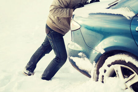transportation, winter and vehicle concept - closeup of man pushing car stuck in snow photo