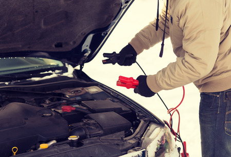 transportation, winter and vehicle concept - closeup of man under bonnet with starter cables Stock Photo