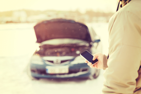 transportation, winter and vehicle concept - closeup of man with broken car and smartphone Imagens