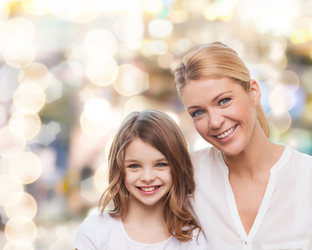 teen girl smile face: family, childhood, happiness and people - smiling mother and little girl over lights background