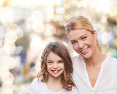 jeune fille adolescente: la famille, l'enfance, le bonheur et les gens - m�re souriante et petite fille sur les lumi�res de fond Banque d'images