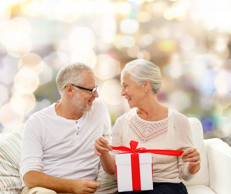vejez feliz: familia, d�as de fiesta, navidad, la edad y el concepto de la gente - la feliz pareja senior con caja de regalo sobre fondo de las luces Foto de archivo