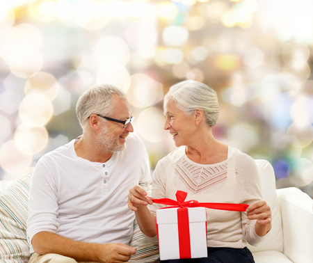 old age home: family, holidays, christmas, age and people concept - happy senior couple with gift box over lights background